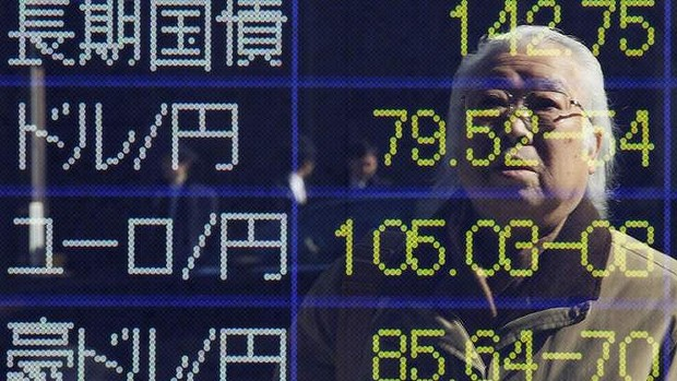 A man is reflected in an electronic board displaying foreign currency rates against the Japanese yen and the Japanese government bond outside a brokerage firm in Tokyo February 20, 2012. Japan's Nikkei share average climbed above its 1-year moving average on Monday after China eased policy to boost growth, while market players looked to a European meeting later in the day to seal a long-awaited Greek bailout. REUTERS/Yuriko Nakao (JAPAN - Tags: BUSINESS EMPLOYMENT POLITICS)