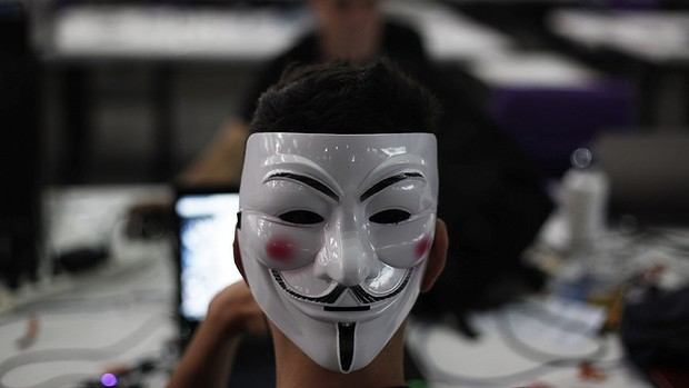 A hacker with a Guy Fawkes mask, a symbol linked to the Anonymous hacking movement.