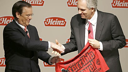 Heinz CEO William Johnson and 3G Capital Managing Partner Alex Behring shake hands